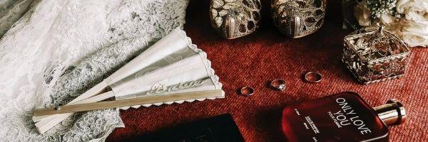fragrance bottle beside the dress and wedding rings